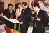 我院美术专业毕业生李定三(左一)将自己的作品向原全国政协主席贾庆林(左三)汇报
